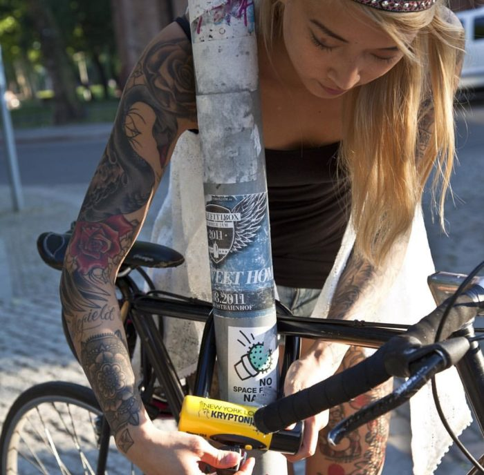 Велосипед пристёгнутый ю-замком к знаку